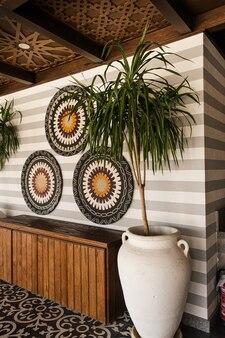 木製の家具、ヤシの植物、壁にカラフルな装飾プレートを備えた伝統的なオリエンタルバーのインテリアデザイン
