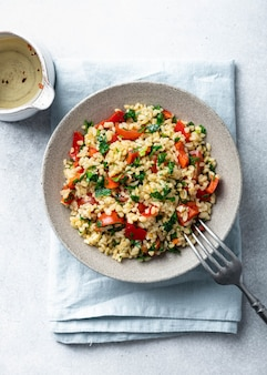 Traditional oriental salad tabouleh with bulgur and parsley on concrete table, view from above