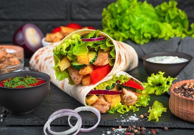 黒い壁に伝統的な東洋のシャワルマのクローズアップ。肉、フライドポテト、野菜、サラダをピタパンで包みました。クイック スナック、ファーストフード。