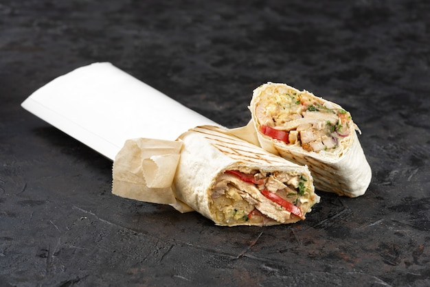 Traditional oriental shawarma in eco-friendly cardboard. dark stone surface. concept of eco packages of recyclables. copy space