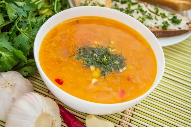 Традиционный восточный суп с помидорами, красной чечевицей, зеленью Premium Фотографии