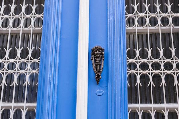 Традиционная декоративная дверная ручка или молоток на фоне окрашенной в синий цвет деревянной двери.