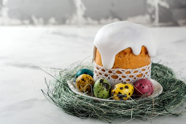 Traditional orthodox easter bread kulich with colorful quail eggs on a light