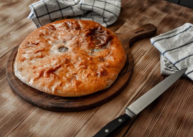 Традиционные осетинские пироги с мясом с говядиной, на деревянном столе. деревенский стиль, крупный план, выборочный фокус
