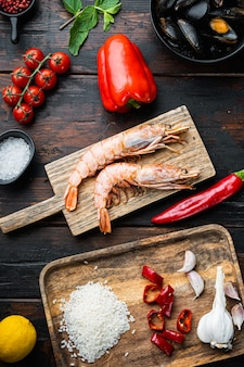 Traditional paella valenciana raw ingredients with shrimps, mussel, rice and squid over dark rustic wooden background