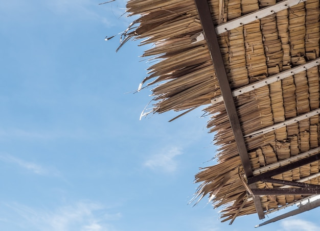 Traditional palm roof under the clear blue sky.