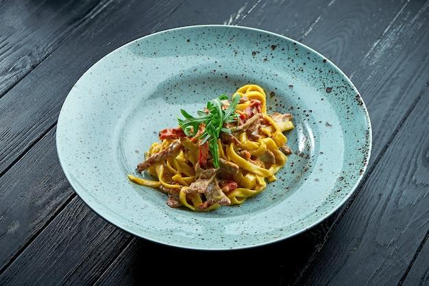 Традиционные спагетти из макарон со сливочным соусом, говядиной и помидорами, рукколой, которые подают в синей тарелке на черном, деревянном фоне. итальянская кухня