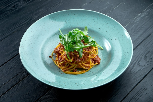 Традиционные спагетти из макарон с фаршем и томатным соусом болоньезе с рукколой, подаваемые в синей тарелке на черном деревянном фоне. итальянская кухня