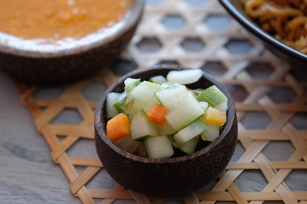 Traditional pickles from indonesia cucumber and carrot in wooden little bowl