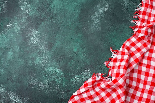 Traditional picnic red checkered fabric tablecloth or napkin on green background