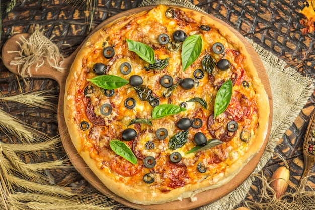 Traditional pizza with cheese, tomatoes, black olives, basil.