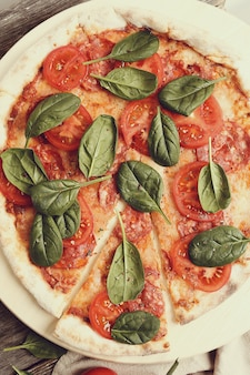 Traditional pizza with tomato slices and basil leaves