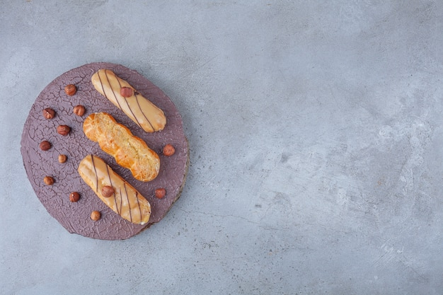 Traditional plain eclairs with hazelnuts placed on a wooden piece .