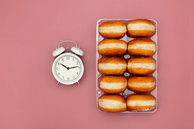 Traditional polish donuts in a box and alarm clock