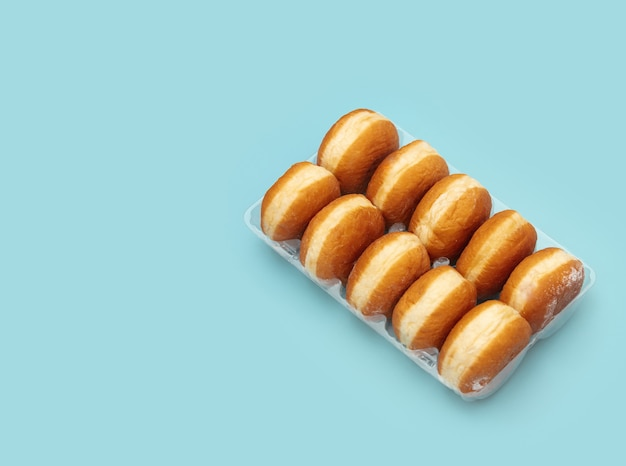 Traditional polish donuts in a box on blue background
