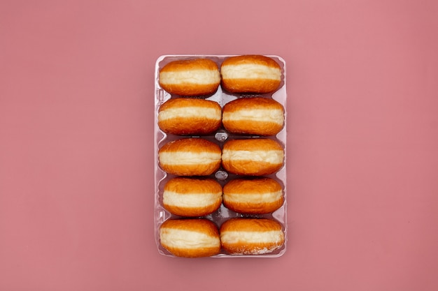 Traditional polish donuts in a box on pink background