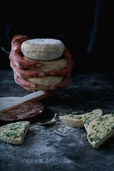 Traditional portuguese flat circular bread bolo do caco. female hands holding stack of the bread. selective focus