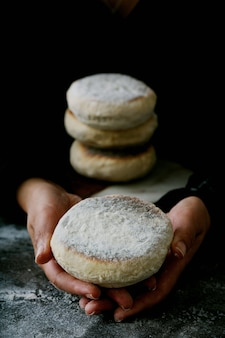Traditional portuguese flat circular bread bolo do caco in female hands. stack of the bread on the desk. selective focus