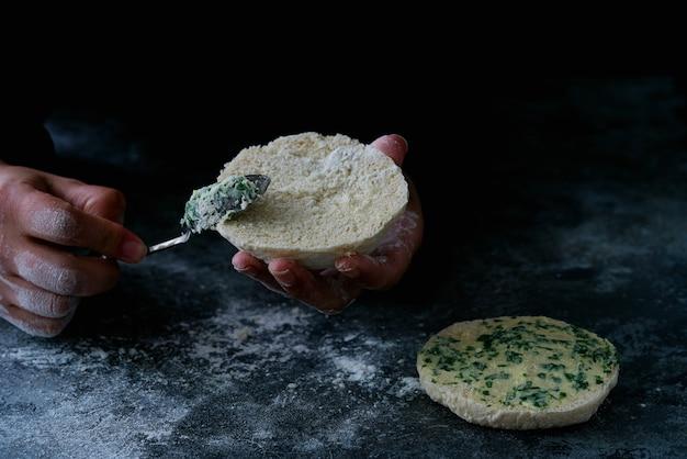 伝統的なポルトガルの平らな円形のパンbolodocaco。パンをバタリングする女性の手。セレクティブフォーカス