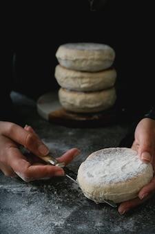 伝統的なポルトガルの平らな円形のパンbolodocaco。パンを切る女性の手。机の上のパンのスタック。セレクティブフォーカス