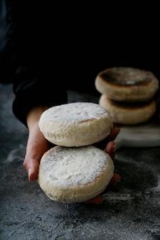 女性の手で伝統的なポルトガルの平らな円形のパンbolodocaco。セレクティブフォーカス