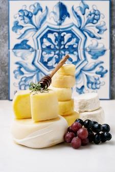 トレイにある伝統的なポルトガルのセミソフトチーズ。新鮮なブドウ、蜂蜜、ハーブを添えて。側面図。セレクティブフォーカス。