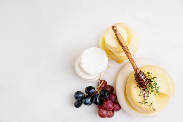 伝統的なポルトガルのセミソフトチーズに、新鮮なブドウ、蜂蜜、ハーブを添えました。上面図。コピースペース