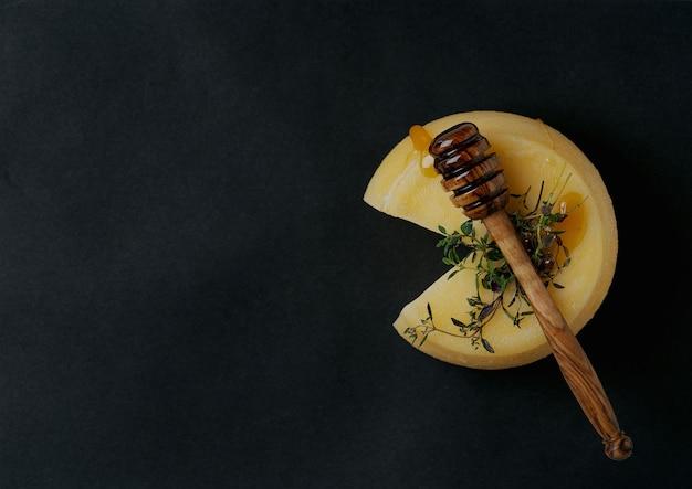蜂蜜、ディッパー、ハーブを添えた伝統的なポルトガルのセミソフトチーズ。上面図。