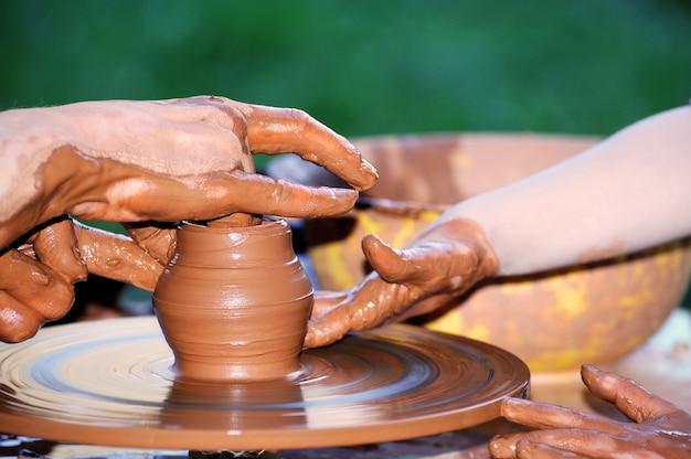 伝統的な陶器作り、ボウルを形作る陶芸家の手のクローズアップ