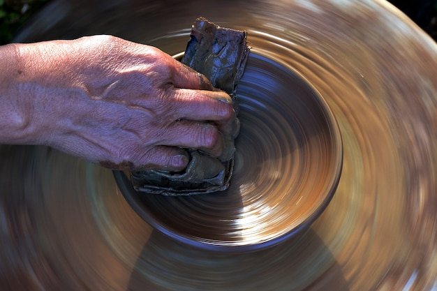 Traditional process of making earthenware from fresh wet clay on pottery wheel