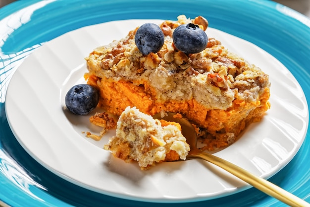Traditional pumpkin dump cake american easy autumn dessert with cinnamon, clove, nutmeg with walnuts and oats on top served on a plate with blueberries on white marble background, close-up