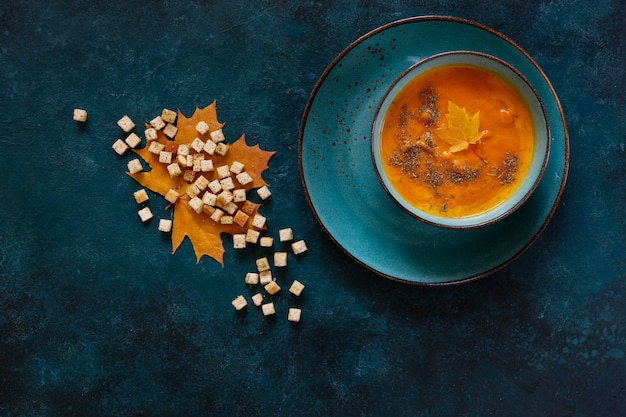 Traditional pumpkin homemade cream-soup with croutons and thyme