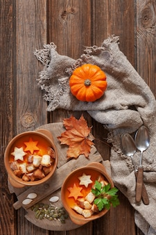 Traditional pumpkin homemade cream-soup with seeds, crackers and  little pumpkin.