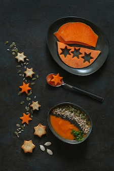 Traditional pumpkin homemade cream-soup with seeds, crackers and pumpkin slices.
