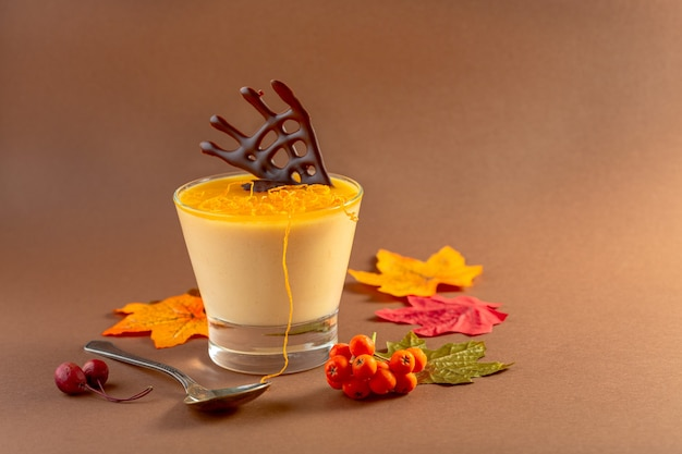 Traditional pumpkin panna cotta with orange jelly and chocolate decor on brown background with copy space. idea of a halloween party.