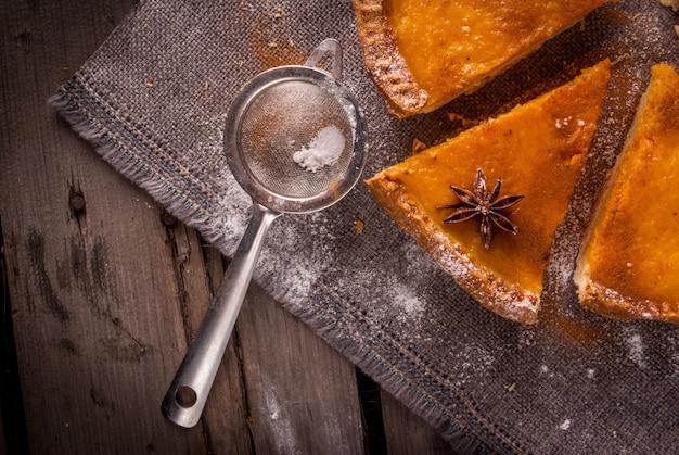 할로윈이나 추수 감사절에 대한 전통적인 호박 파이. 나무 테이블에 소박한 스타일입니다. 평면도, 복사 공간