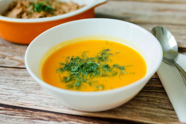 Традиционный тыквенный суп с семенами, укропом на деревянном столе.