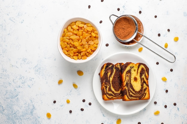 Traditional raisin marble cake slices with raisins and cocoa powder, top view
