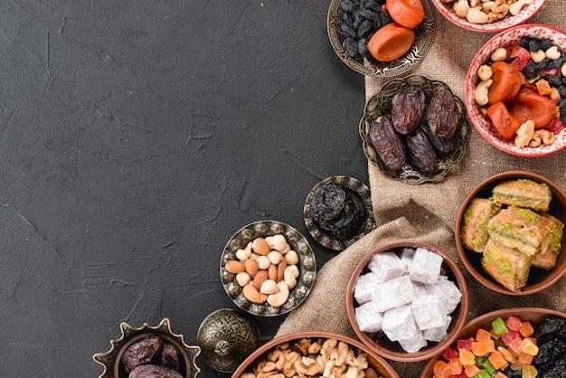 검은 배경에 금속 및 흙 그릇에 전통적인 라마단 디저트와 견과류