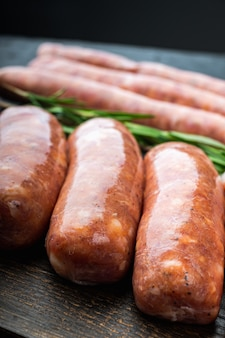 Traditional raw pork sausages, on black table