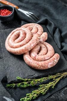 Traditional raw spiral chicken sausages. black background.