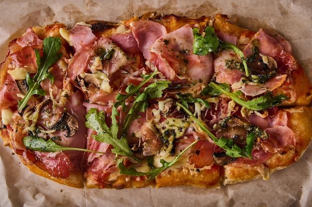 Traditional rectangular roman pizza with prosciutto ham tomatoes mozzarella mushrooms and arugula