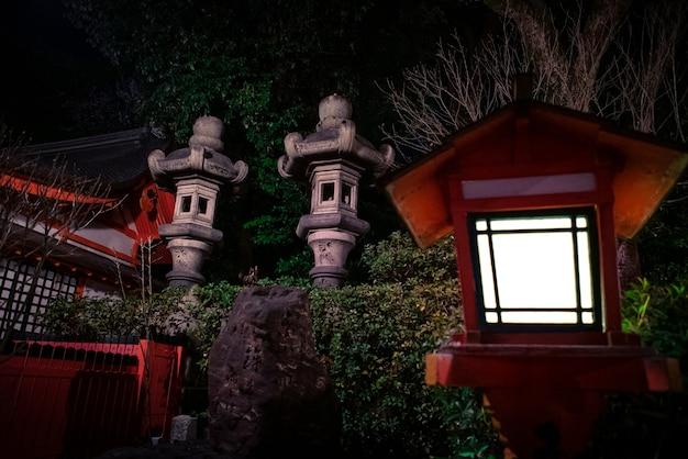 Традиционные красные японские фонарные столбы в храме ясака ночью. храм гион - одна из самых известных святынь в киото.