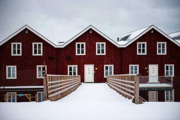 ドアに直接つながる小さな木製の橋がある伝統的な赤いノルウェーの家。周りの冬の雰囲気。ロフォーテン島の美しいディテール。
