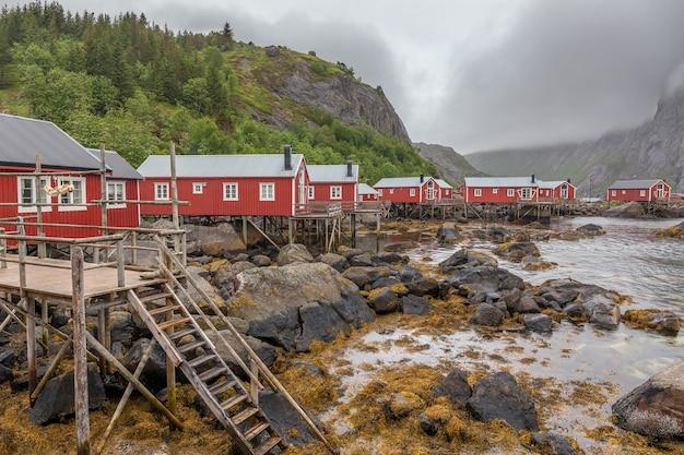 Традиционные красные деревянные дома, rorbuer в небольшой рыбацкой деревушке нусфьорд, лофотенские острова, норвегия.