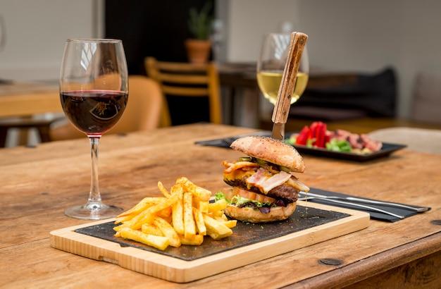 Традиционная атмосфера ресторана с чипсами и тарелкой татаки из тунца на фоне деревенского деревянного стола и бокалом красного вина