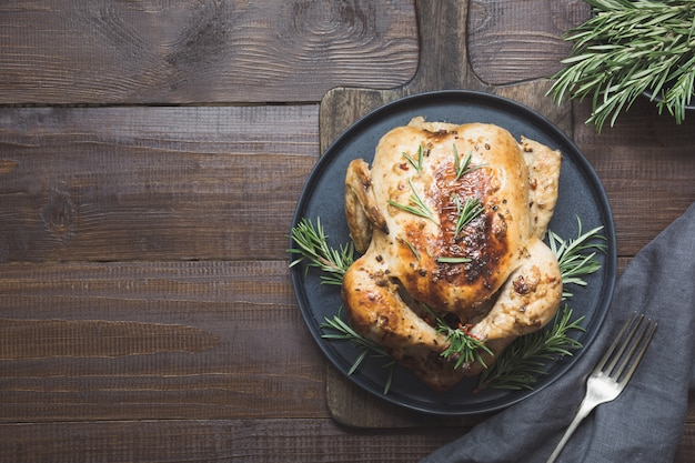 Traditional roasted chicken garnish rosemary on wooden table. top view.