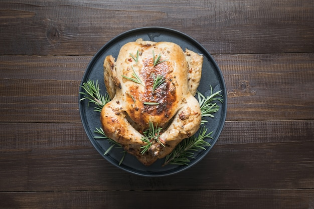 Traditional roasted chicken with rosemary on wooden table. top view.