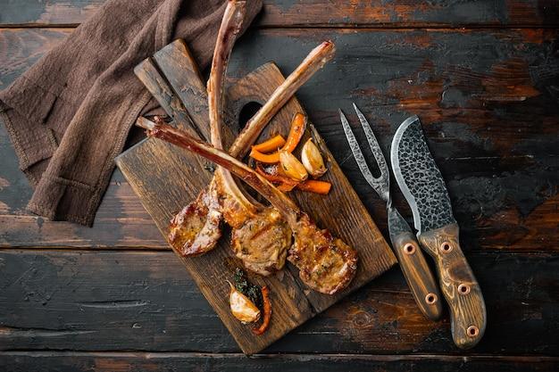 전통적인, 구운 양고기 커틀릿 랙, 나무 서빙 보드, 오래 된 어두운 나무 테이블, 평면도 평면 누워