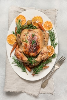 Traditional roasted turkey with rosemary on light table. top view.